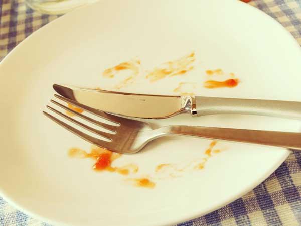 料理を食べ終わった皿の上に置かれたフォークとナイフ