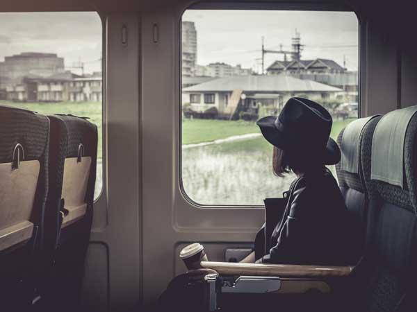 電車に乗る遠距離恋愛の女性
