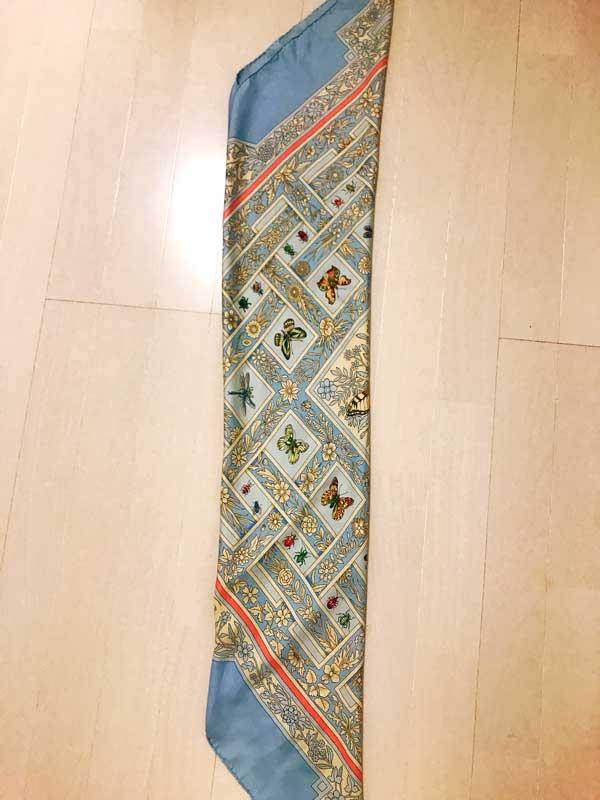 対角の山が重ならないように内側に折り合わせたスカーフを2つ折りにした状態