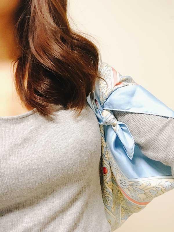 スカーフの両端を結んで中央にできた穴から左腕を通した様子