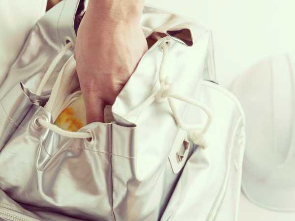 災害時に必要な物を持出袋に入れる男性の手