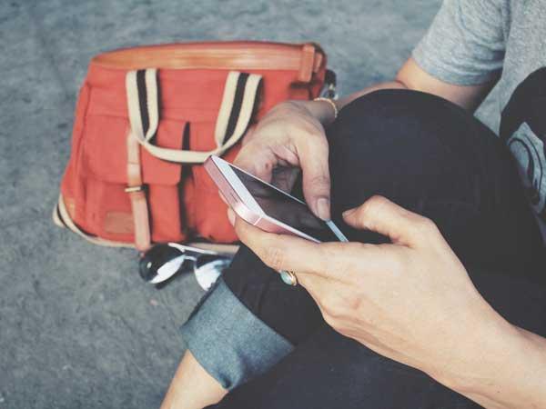 携帯をいじる女性の手