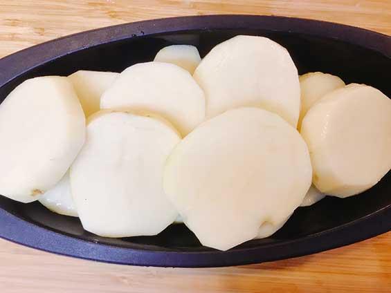 時短で加熱できるようにスライスして耐熱容器に並べたジャガイモ