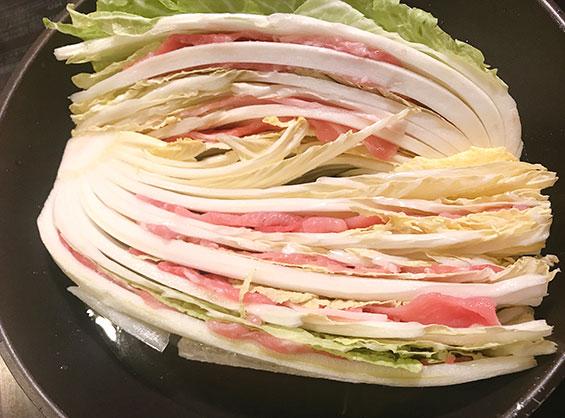 フライパンに豚肉をミルフィーユ状に挟んだ白菜を並べた状態