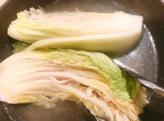 火が通った白菜と豚肉をフライパンから取り出している様子