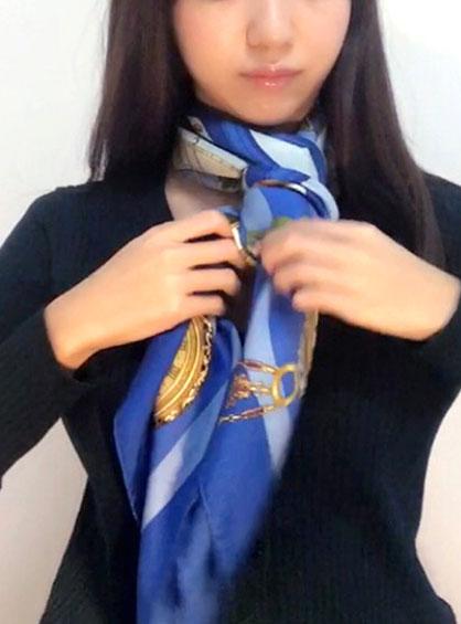 右側に持ってきたスカーフを首に巻いたスカーフの中央部分で下から上へ通した様子