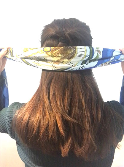 スカーフをバンダナ風にアレンジする手順1バイアス折りにしたスカーフを後ろから頭に巻きつけている様子