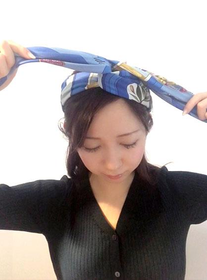 スカーフのバンダナ風アレンジ手順3スカーフの両橋を掴み崩れないように頭頂部でもう一度交差している様子