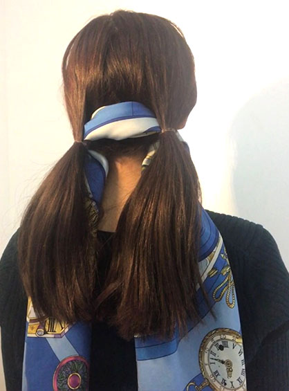 スカーフくるりんぱアレンジの手順3左右の毛束を一本に繋ぐように両方の結び目の上からバイアス折にしたスカーフを通す