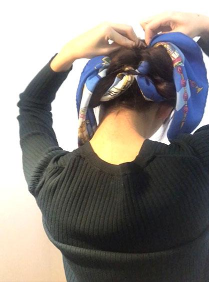スカーフくるりんぱシニヨンアレンジの手順6スカーフの毛束が真ん中にくるように、三つ編みした毛束をクルクル巻いたら襟足をピンで固定する