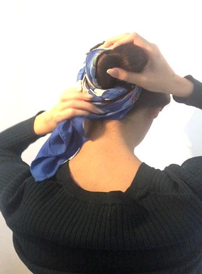 三つ編みシニヨン手順4編んだ毛束を丸めてお団子を作りスカーフの端を結ぶかピンで留める